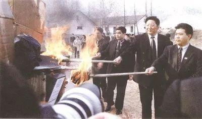 奥康集团董事长王振滔,和温州市、永嘉县领导一起,用长长的点火棒,烧毁了在全国各地查获到的2000多双假冒奥康皮鞋,以及数